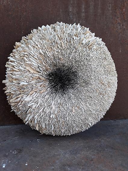Black center sculpture by Emanuela Camacci. Circular shape sculpture made with limestone chips